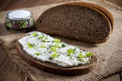 Sandwich with cream, dill and chives and dark rye bread and salt in saltshaker on burlap. Close-up.  stock photos