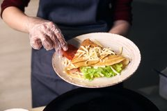 Sandwich crepe rolled up with vegetables and serving in white plate. Traditional hot breakfast food. Close up view. Cropped view of chef decorate in white plate royalty free stock photo