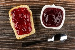 Sandwich with currant jam, bowl with jam, spoon on wooden table. Top view. Sandwich with currant jam, bowl with jam, teaspoon on dark wooden table. Top view stock photography