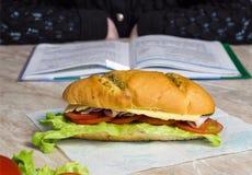 Sandwich dans le premier plan, à l'arrière-plan une fille faisant l'école de devoirs images libres de droits