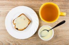 Sandwich de petit pain avec du lait condensé dans le plat, thé Photographie stock libre de droits