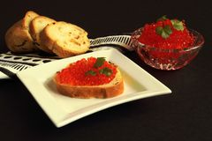 Sandwich with delicious red salmon caviar on white porcelain plate of unusual shape, white baguette on paper napkin with geometric stock image
