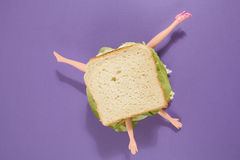 Sandwich doll. Parts of a doll`s body in a sandwich with salad and soft bread on a minimal background color Stock Photo
