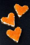 Sandwich drie met rode kaviaar in de vorm van een hart op een zwarte Stock Afbeelding