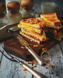 Sandwich with egg, tomato, onions and bacon on a vintage wooden Stock Photos