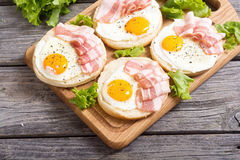 Sandwich with eggs and bacon. On wooden table Royalty Free Stock Photos