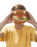 Sandwich Face. Boy holding giant sandwich up to his mouth, hiding his entire face Royalty Free Stock Images