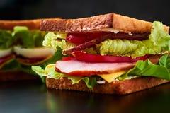 Sandwich fait maison avec de la laitue et le jambon sur un fond noir, fin  photographie stock libre de droits