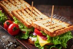 Sandwich fait maison avec du jambon, la laitue, le fromage et la tomate sur un fond en bois photographie stock libre de droits