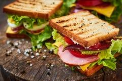 Sandwich fait maison avec du jambon, la laitue, le fromage et la tomate sur un fond en bois photos libres de droits