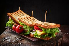 Sandwich fait maison avec du jambon, la laitue, le fromage et la tomate sur un fond en bois photographie stock