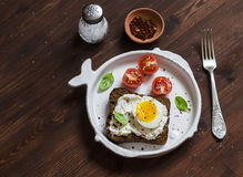 Sandwich with feta cheese and boiled egg, tomatoes, and basil on a white plate on a dark wooden surface. Stock Photo