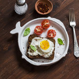 Sandwich with feta cheese and boiled egg, tomatoes, and basil on a white plate on a dark wooden surface. Royalty Free Stock Photos