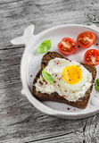 Sandwich with feta cheese and boiled egg, tomatoes, and basil on a white plate on a wooden surface. Royalty Free Stock Photo