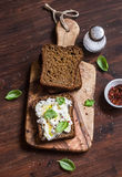 Sandwich with feta cheese, olive oil and basil, served on olive cutting board on dark wooden surface. Stock Photos