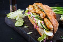 sandwich with fish, egg, pickled onions and lettuce leaves. Stock Photo