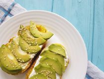 Sandwich freshwith avocado organic closeup and sesame seeds veggie toast on a wooden. Sandwich fresh avocado and se closeupsame seeds cheese toast   on a wooden Royalty Free Stock Photo