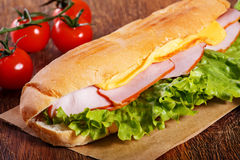 Sandwich from fresh baguette on wooden background. Sandwich from fresh baguette with lettuce, slices of fresh tomatoes, ham and cheese on wooden background Stock Images