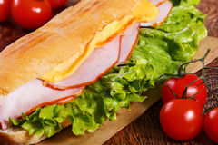 Sandwich from fresh baguette on wooden background. Sandwich from fresh baguette with lettuce, slices of fresh tomatoes, ham and cheese on wooden background Royalty Free Stock Photos