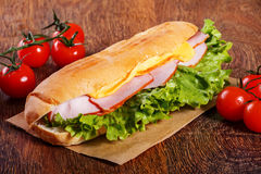 Sandwich from fresh baguette on wooden background. Sandwich from fresh baguette with lettuce, slices of fresh tomatoes, ham and cheese on wooden background Royalty Free Stock Images