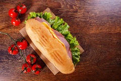 Sandwich from fresh baguette on wooden background. Sandwich from fresh baguette with lettuce, slices of fresh tomatoes, ham and cheese on wooden background Stock Photo