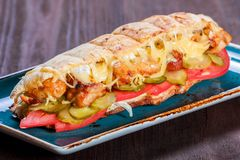 Sandwich from fresh pita bread with fillet grilled chicken, lettuce, slices of fresh tomatoes. Pickles and cheese on dark wooden background. Shashlik or Shish royalty free stock photography