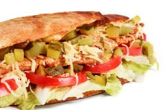 Sandwich from fresh pita bread with fillet grilled chicken, lettuce, slices of fresh tomatoes. Pickles and cheese on white background royalty free stock photography