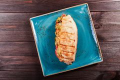 Sandwich from fresh pita bread with fillet grilled chicken, lettuce, slices of fresh tomatoes, pickles and cheese. On dark wooden background. Shashlik or Shish royalty free stock photography