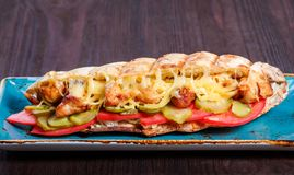 Sandwich from fresh pita bread with fillet grilled chicken, lettuce, slices of fresh tomatoes, pickles. And cheese on dark wooden background. Shashlik or Shish stock photo