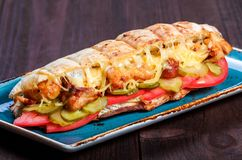 Sandwich from fresh pita bread with fillet grilled chicken, lettuce, slices of fresh tomatoes,. Pickles and cheese on dark wooden background. Shashlik or Shish royalty free stock photography