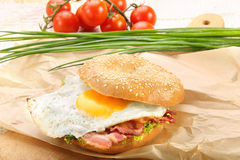 Sandwich with fried bacon and egg on a chopping board Stock Image