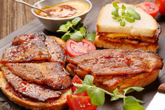 Sandwich with fried bacon on wooden background Royalty Free Stock Image