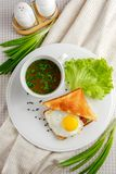 Sandwich with a fried egg and mug of soup. Sandwich with a fried egg and a mug of soup on a white plate with lettuce and green onions decorated with textile Stock Photography