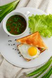 Sandwich with a fried egg and mug of soup. Sandwich with a fried egg and a mug of soup on a white plate with lettuce and green onions decorated with textile Royalty Free Stock Image