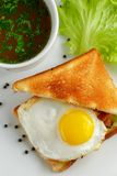 Sandwich with a fried egg and mug of soup. Sandwich with a fried egg and a mug of soup on a white plate with lettuce leaves and black pepper, close-up view from Royalty Free Stock Photography