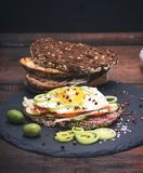 Sandwich with fried egg and a piece of rye bread. With vegetables, vintage toning Royalty Free Stock Image