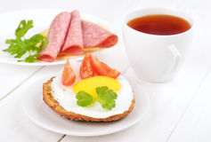 Sandwich with fried egg, tomato slices and tea Royalty Free Stock Photography