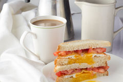 Sandwich with fried egg and tomatoes and cup of coffee Stock Images