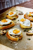 Sandwich with fried quail eggs, mushrooms and toast. On a rustic pan Royalty Free Stock Photography