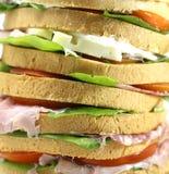 Sandwich géant bourré de beaucoup de couches de pain avec de la laitue à Photographie stock