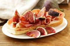 Sandwich gastronome avec du jambon fumé (Parme) et des figues Images stock