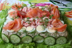 Sandwich gateau. Delicious sandwich gateau, with smoked salmon, shrimps, egg, tomato cucumber and so on, is standing on laid table Stock Images