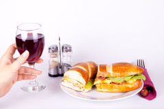 Sandwich and glass of wine. Delicius sandwich on plate and a hand holding a glass of wine Stock Photography
