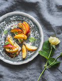 Sandwich with goat cheese and peach on a vintage plate on a gray background Royalty Free Stock Photo