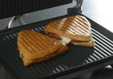 Sandwich on griddle. A meat and cheese sandwich is heated on a griddle Stock Images