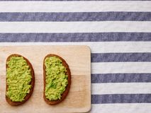 Sandwich with guacamole on light textile background top view. sandwiches on wooden board stock photography