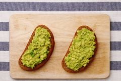 Sandwich with guacamole on wood top view.  royalty free stock image