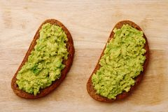 Sandwich with guacamole on wood top view. Avocado on sandwich stock images
