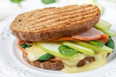 Sandwich with ham, brie cheese or Camembert, spinach, Apple and mustard. Gourmet Breakfast closeup. Selective focus Royalty Free Stock Photography