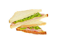 Sandwich with ham and cheese. Here's two sandwiches with ham, swiss cheese and lettuce leaf, isolated on white Royalty Free Stock Photography